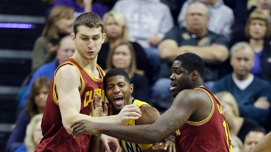 Indiana Pacers' Paul George, middle, battles for a loose ball against Cleveland Cavaliers' Tyler Zeller, left, and Anthony Bennett during the first half of an NBA basketball game Saturday, Nov. 2, 2013, in Indianapolis. (AP Photo/Darron Cummings)