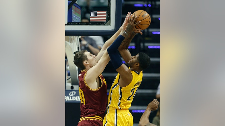 Indiana Pacers' Paul George, right, puts up a shot against Cleveland Cavaliers' Tyler Zeller during the first half of an NBA basketball game Saturday, Nov. 2, 2013, in Indianapolis. (AP Photo/Darron Cummings)