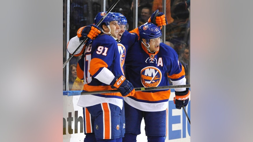 New York Islanders' John Tavares (91), Thomas Vanek, center, and Kyle Okposo (21) celebrate Vanek's first goal as an Islander against the Boston Bruins in the second period of an NHL hockey game at the Nassau Coliseum on Saturday, Nov. 2, 2013, in Uniondale, N.Y. (AP Photo/Kathy Kmonicek)