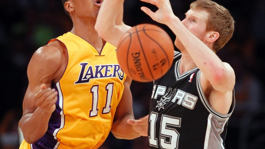 Los Angeles Lakers guard Wesley Johnson (11) knocks the ball away from San Antonio Spurs forward Matt Bonner (15) in the second quarter of an NBA basketball game Friday, Nov. 1, 2013, in Los Angeles. (AP Photo/Alex Gallardo)
