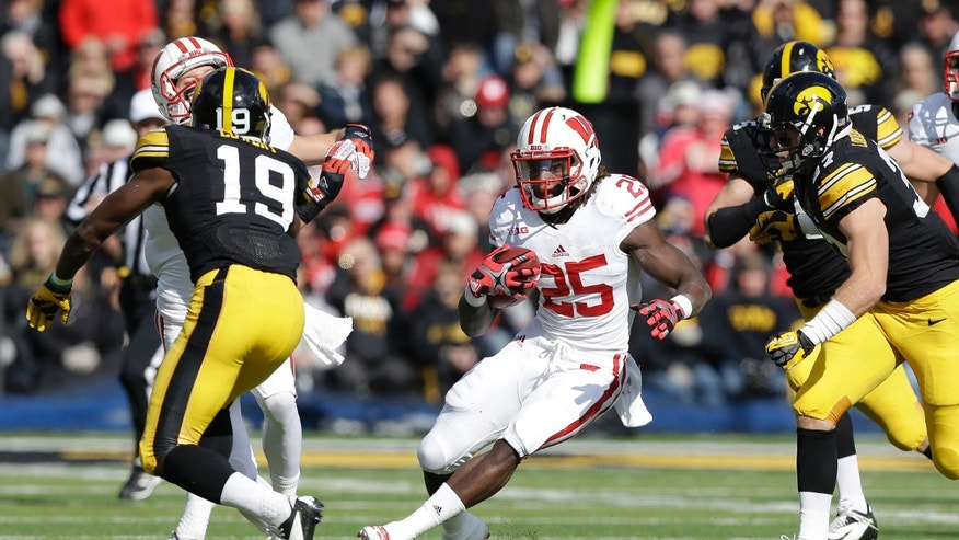 Wisconsin running back Melvin Gordon (25) runs from Iowa defenders B.J. Lowery (19) and John Lowdermilk, right, during the first half of an NCAA college football game, Saturday, Nov. 2, 2013, in Iowa City, Iowa. (AP Photo/Charlie Neibergall)
