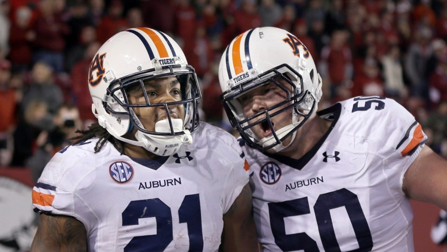 Auburn center Reese Dismukes (50) celebrates with running back Tre Mason (21) after Mason's fourth quarter touchdown in an NCAA college football game in Fayetteville, Ark., Saturday, Nov. 2, 2013. Auburn won 35-17. (AP Photo/Danny Johnston)