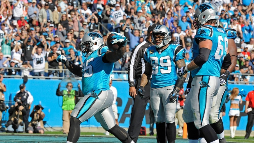 Carolina Panthers' Mike Tolbert (35) celebrates his touchdown run against the Atlanta Falcons in the first half of an NFL football game in Charlotte, N.C., Sunday, Nov. 3, 2013. Carolina Panthers' Steve Smith (89) and Jordan Gross (69) look on. (AP Photo/Mike McCarn)