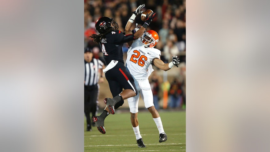 Texas Tech's Bradley Marquez (4) reaches for the ball as Tyler Patmon (26) is called for interference during their NCAA college football game against Oklahoma State, in Lubbock, Texas, Saturday, Nov. 2, 2013. (AP Photo/Lubbock Avalanche-Journal,Stephen Spillman)