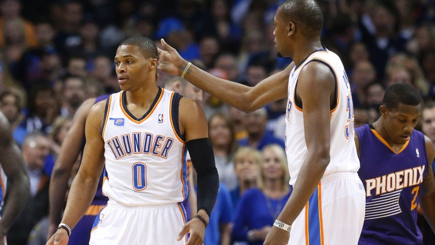 Oklahoma City Thunder forward Kevin Durant (35) pats teammate Russell Westbrook (0) on the head during the first quarter of an NBA basketball game against the Phoenix Suns in Oklahoma City, Sunday, Nov. 3, 2013. (AP Photo/Sue Ogrocki)