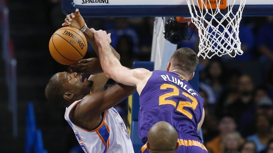 Oklahoma City Thunder forward Kevin Durant (35) is fouled by Phoenix Suns center Miles Plumlee (22) as he shoots in the first quarter of an NBA basketball game in Oklahoma City, Sunday, Nov. 3, 2013. (AP Photo/Sue Ogrocki)