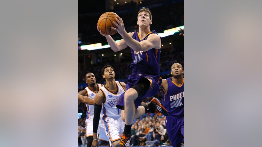 Phoenix Suns guard Goran Dragic (1) shoots in front of Oklahoma City Thunder guard Jeremy Lamb (11) and forward P.J. Tucker (17) in the second quarter of an NBA basketball game in Oklahoma City, Sunday, Nov. 3, 2013. (AP Photo/Sue Ogrocki)