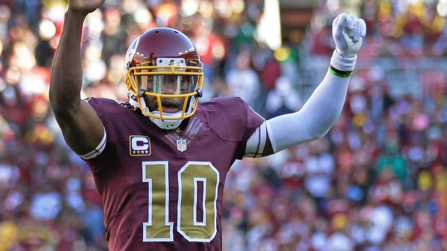 Washington Redskins quarterback Robert Griffin III celebrates a touchdown by fullback Darrel Young during the second half of a NFL football game against San Diego Chargers in Landover, Md., Sunday, Nov. 3, 2013. (AP Photo/Patrick Semansky)