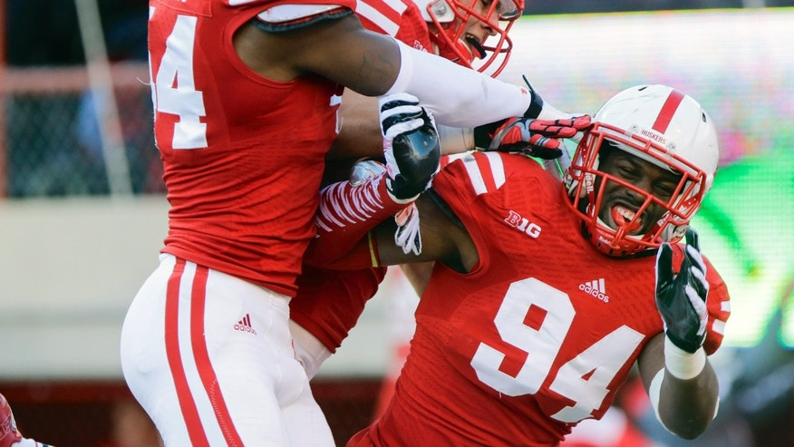 Nebraska defensive end Randy Gregory, left, and linebacker Josh Banderas, center, celebrate with defensive end Avery Moss (94) after Moss intercepted a throw by Northwestern quarterback Kain Colter for a touchdown in the second half of an NCAA college football game in Lincoln, Neb., Saturday, Nov. 2, 2013. Nebraska won 27-24. (AP Photo/Nati Harnik)