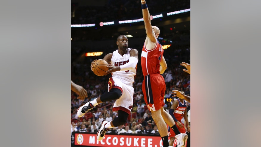 Miami Heat's Dwyane Wade (3) goes around Washington Wizards' Marcin Gortat (4) for two points during the first half of an NBA basketball game in Miami, Sunday, Nov. 3, 2013. (AP Photo/J Pat Carter)