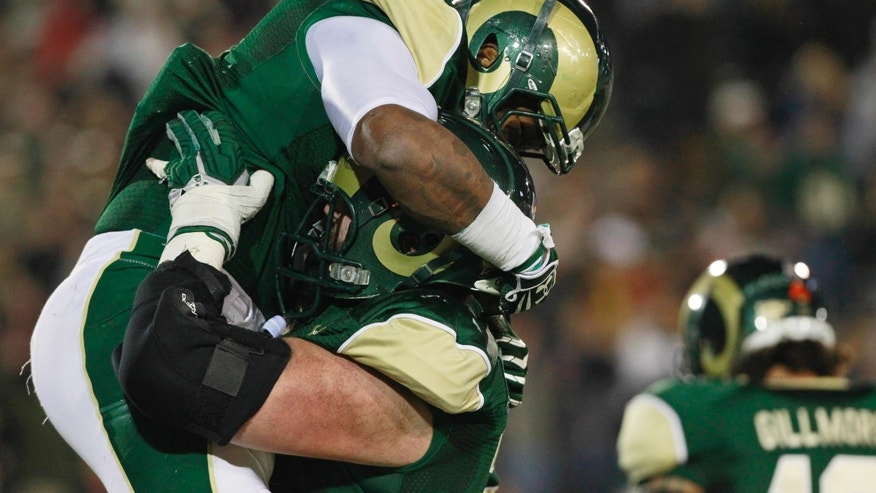 Colorado State running back Kapri Bibbs, left, celebrates his touchdown run with offensive lineman Jared Biard against Boise State in the first quarter of an NCAA college football game in Fort Collins, Colo., on Saturday, Nov. 2, 2013. (AP Photo/David Zalubowski)