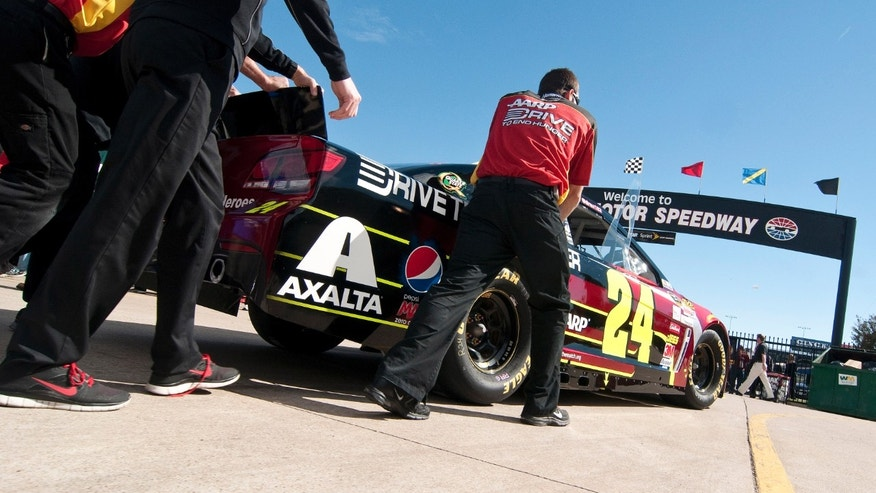 Crew members roll Jeff Gordon's car to an inspection before the NASCAR Sprint Cup series auto race at Texas Motor Speedway in Fort Worth, Texas, Sunday, Nov. 3, 2013. (AP Photo/Ralph Lauer)