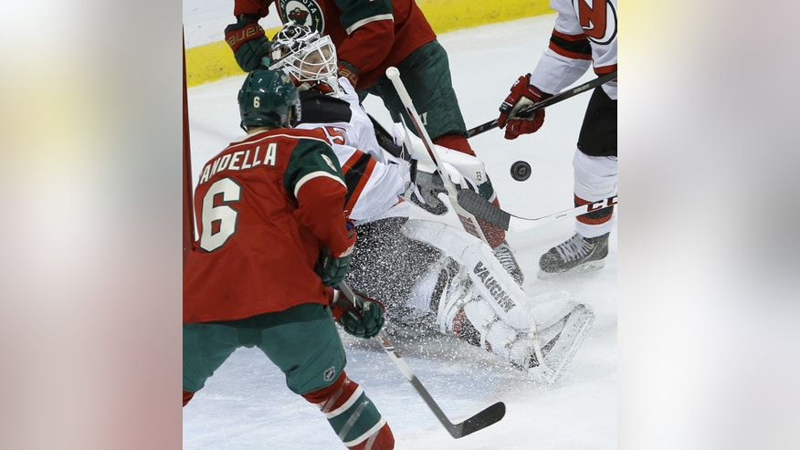 New Jersey Devils goalie Cory Schneider (35) deflects a shot as Minnesota Wild defenseman Marco Scandella (6) watches during the first period of an NHL hockey game in St. Paul, Minn., Sunday, Nov. 3, 2013. (AP Photo/Ann Heisenfelt)