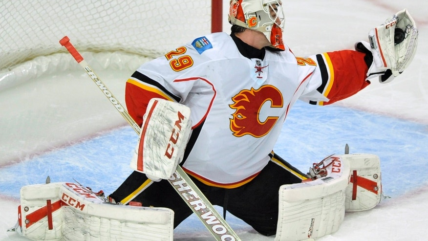 Calgary Flames goalie Reto Berra of Switzerland, makes a save during the first period of an NHL hockey game against the Chicago Blackhawks in Chicago, Sunday, Nov. 3, 2013. (AP Photo/Paul Beaty)