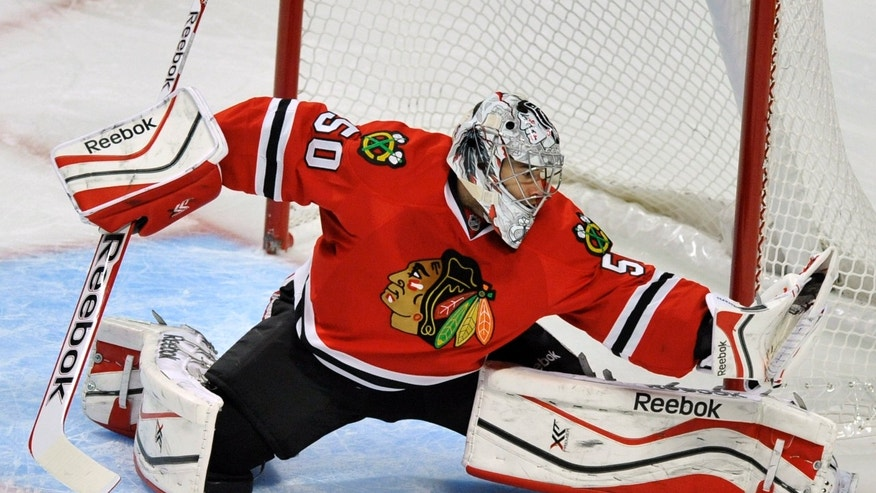 Chicago Blackhawks goalie Corey Crawford makes a save during the first period of an NHL hockey game against the Calgary Flames in Chicago, Sunday, Nov. 3, 2013. (AP Photo/Paul Beaty)