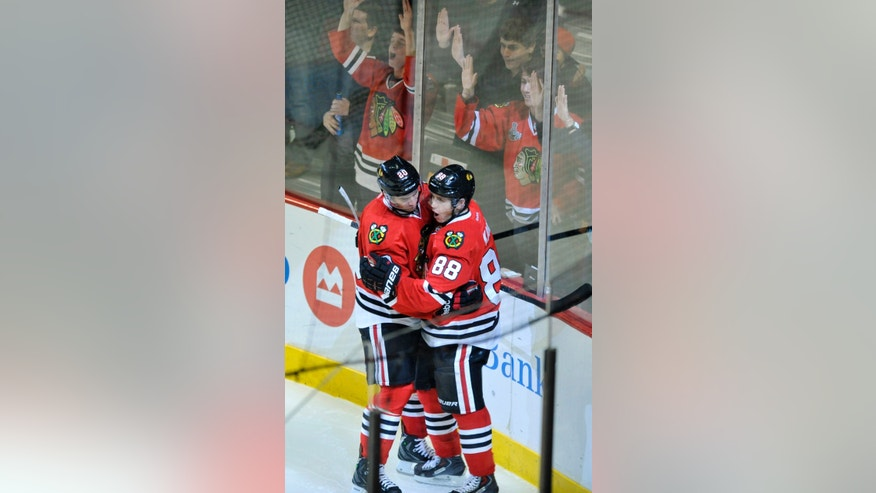 Chicago Blackhawks' Patrick Kane (88), celebrates with teammate Brandon Saad after scoring a goal during the second period of an NHL hockey game against the Calgary Flames in Chicago, Sunday, Nov. 3, 2013. (AP Photo/Paul Beaty)