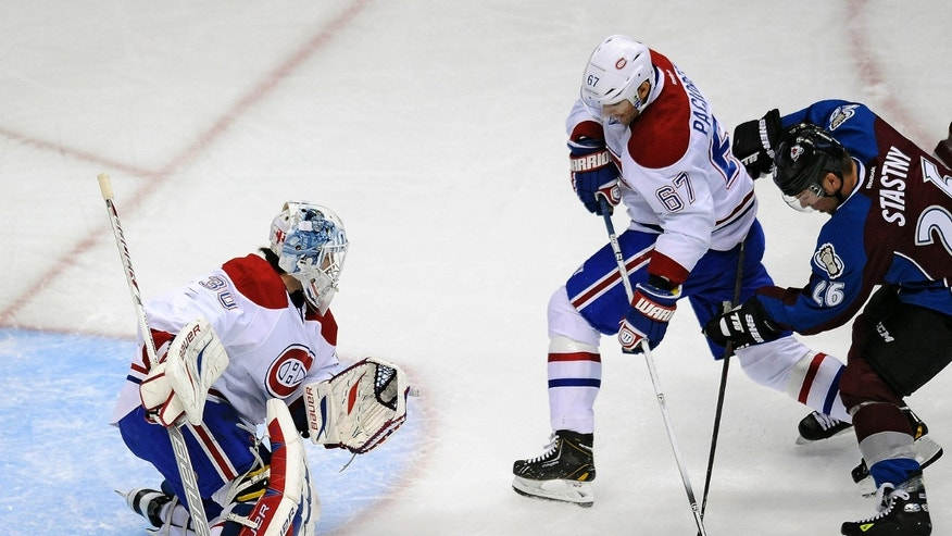 Colorado Avalanche center Paul Stastny, right, and Montreal Canadiens left wing Max Pacioretty, center, fight for the puck in front of Canadiens goalie Peter Budaj, left, in the first period of an NHL hockey game on Saturday, Nov. 2, 2013, in Denver.  (AP Photo/Chris Schneider)