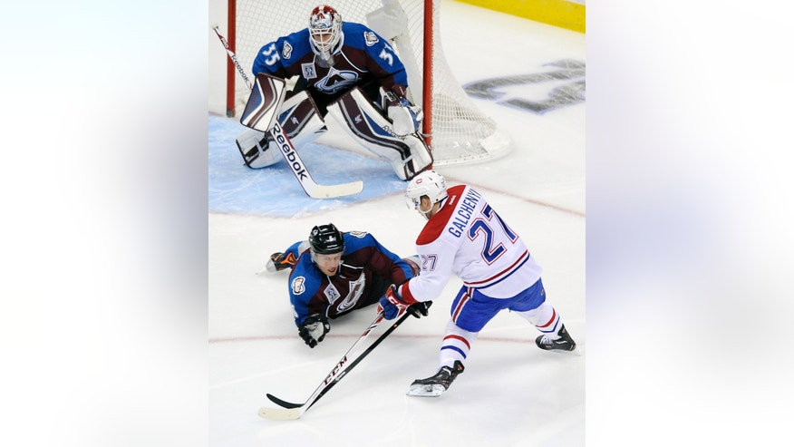 Montreal Canadiens center Alex Galchenyuk, bottom right, tries to shoot the puck against Colorado Avalanche goalie Jean-Sebastien Giguere, top, as Colorado defenseman Erik Johnson,  bottom left, dives in front of the goal in the first period of an NHL hockey game on Saturday, Nov. 2, 2013, in Denver.  (AP Photo/Chris Schneider)