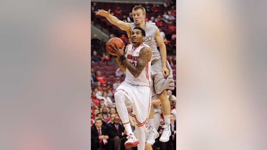 Ohio State's LaQuinton Ross, front, tries to shoot in front of Walsh's Lucas Strouble during the second half of an exhibition NCAA college basketball game Sunday, Nov. 3, 2013, in Columbus, Ohio. Ohio State beat Walsh 93-63. (AP Photo/Jay LaPrete)