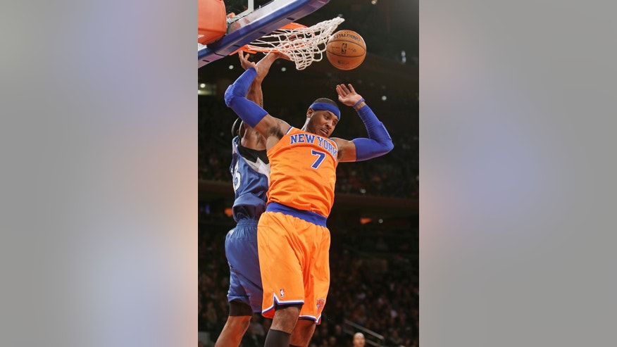 New York Knicks' Carmelo Anthony (7) drives past Minnesota Timberwolves' Dante Cunningham to dunk the ball during the first half of an NBA basketball game Sunday, Nov. 3, 2013, in New York. (AP Photo/Frank Franklin II)