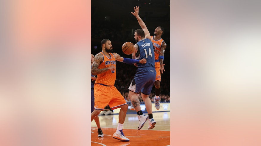 New York Knicks' Iman Shumpert, right, passes around Minnesota Timberwolves' Nikola Pekovic (14) to Tyson Chandler (6) during the first half of an NBA basketball game Sunday, Nov. 3, 2013, in New York. (AP Photo/Frank Franklin II)