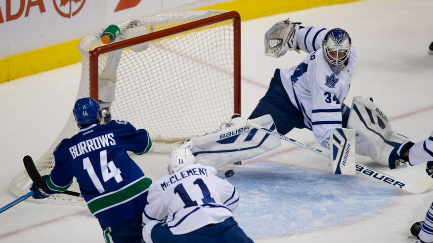 Toronto Maple Leafs goalie James Reimer, right, stops Vancouver Canucks' Alex Burrows, left, as Jay McClement defends during the first period of an NHL hockey game in Vancouver, British Columbia, on Saturday, Nov. 2, 2013. (AP Photo/The Canadian Press, Darryl Dyck)