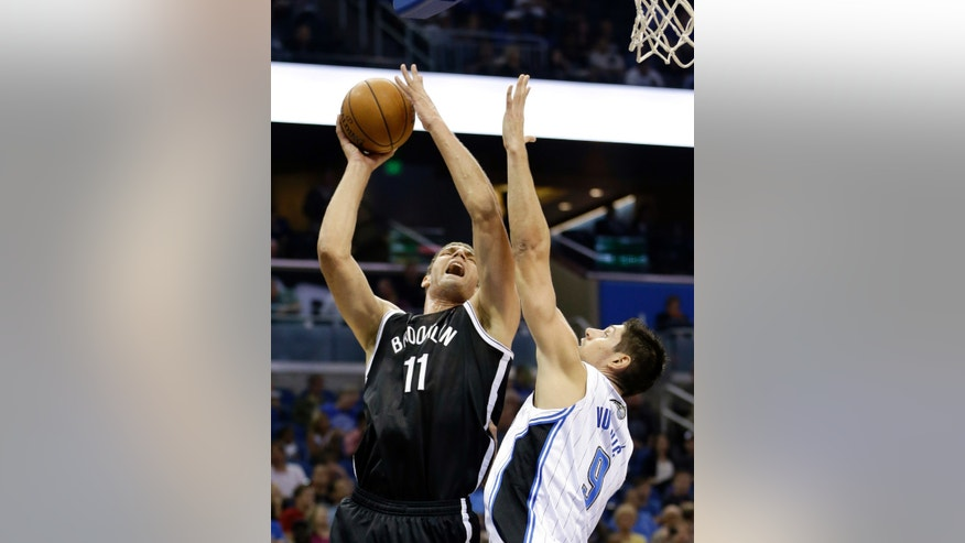 Brooklyn Nets' Brook Lopez (11) attempts a shot over Orlando Magic's Nikola Vucevic, of Montenegro, during the first half of an NBA basketball game in Orlando, Fla., Sunday, Nov. 3, 2013. (AP Photo/John Raoux)