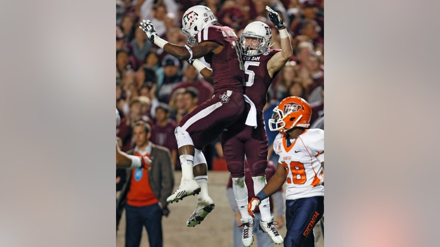 Texas A&M's Travis Labhart, center, celebrates his 44-yard touchdown reception with teammate Derel Walker as UTEP's Demaracus Kizzie looks on during the first half of an NCAA college football game, Saturday, Nov. 2, 2013 in College Station, Texas. (AP Photo/Eric Christian Smith)