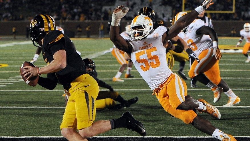 Missouri quarterback Maty Mauk, left, scrambles away from Tennessee defensive lineman Jacques Smith (55) during the second half of an NCAA college football game Saturday, Nov. 2, 2013, in Columbia, Mo. (AP Photo/L.G. Patterson)