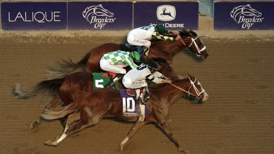 November 2, 2013: Jockey Gary Stevens, top, rides Mucho Macho Man to victory in the Breeders' Cup Classic horse race ahead of Will Take Charge, bottom, and Declaration of War at Santa Anita Park. (AP Photo/Jae C. Hong)