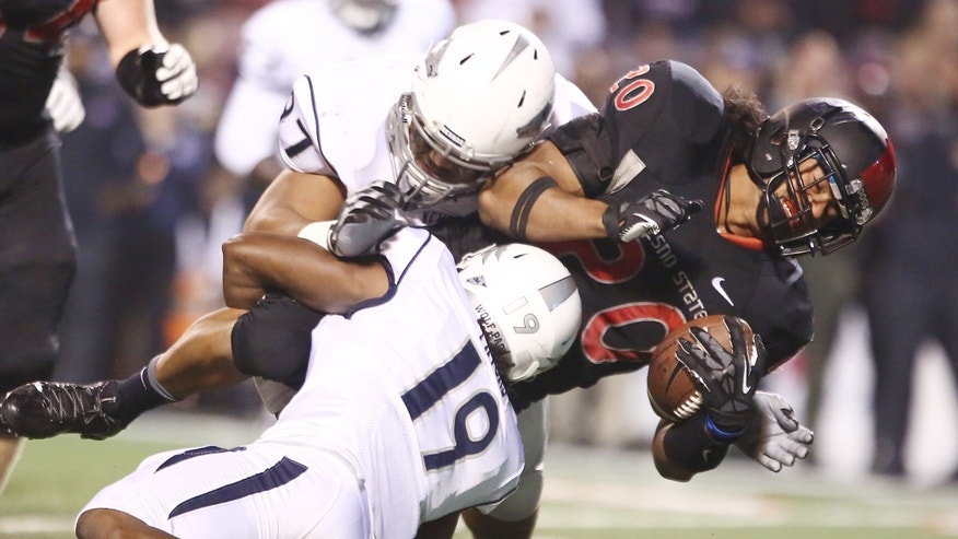 Fresno State's Josh Quezada, right, is tackled by Nevada's Jayden Sawyer after gaining a first down in the first half of an NCAA college football game in Fresno, Calif., Saturday, Nov. 2, 2013. (AP Photo/Gary Kazanjian)