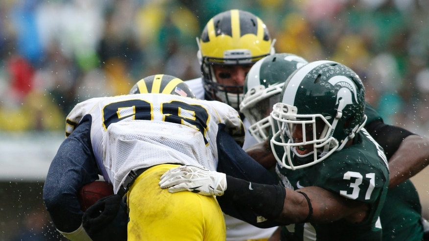 Michigan State's Darqueze Dennard (31) and Isaiah Lewis tackle Michigan quarterback Devin Gardner (98) during the second quarter of an NCAA college football game, Saturday, Nov. 2, 2013, in East Lansing, Mich. Michigan State won 29-6. (AP Photo/Al Goldis)