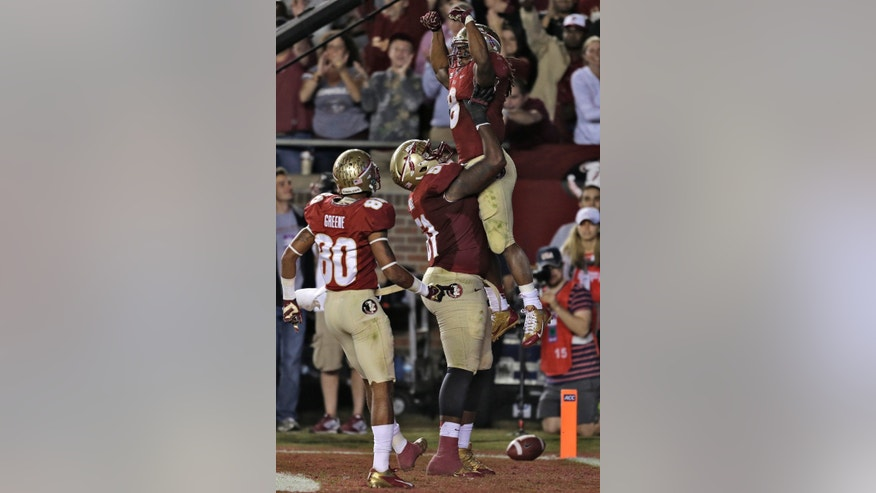Florida State running back Devonta Freeman (8) gets listed off the ground by offensive linesman Bobby Hart (51) after scoring a touchdown against Miami during the third quarter of an NCAA college football game Saturday, Nov. 2, 2013, in Tallahassee, Fla. Also celebrating is wide receiver Rashad Greene (80). (AP Photo/Chris O'Meara)