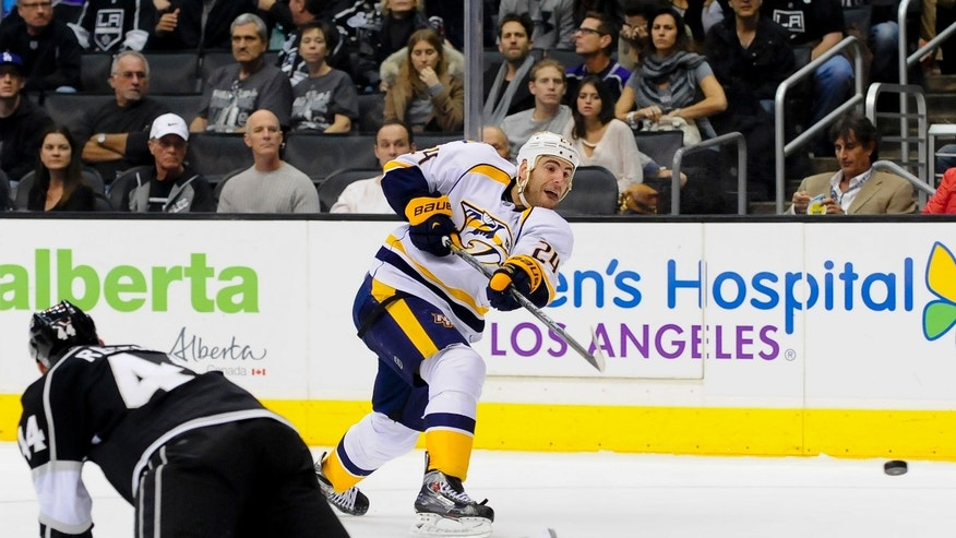 Nashville Predators left wing Eric Nystrom (24) takes a shot after Los Angeles Kings defenseman Robyn Regehr (44), of Brazil, falls leaving an opening during the first period of their NHL hockey game, Saturday, Nov. 2, 2013, in Los Angeles. (AP Photo/Gus Ruelas)