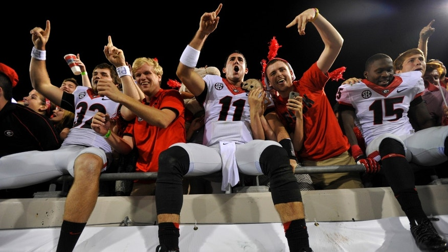 Georgia's Collin Barber (32),  Aaron Murray (11) and  J.J. Green (15) celebrate in the stands with Georgia fans after their 23-20 win over Florida in an NCAA college football game in Jacksonville, Fla., Saturday, Nov. 2, 2013.  (AP Photo/Athens Banner-Herald, AJ Reynolds)  MAGS OUT; MANDATORY CREDIT