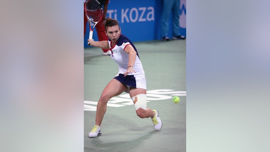 Simona Halep of Romania returns a shot against Samantha Stosur of Australia in the final of the WTA Tournament of the Champions in Sofia, Bulgaria,  Sunday, Nov. 3, 2013. (AP Photo/ Valentina Petrova)