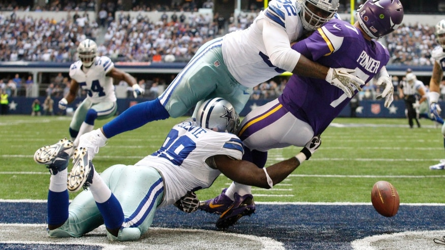 Dallas Cowboys' George Selvie (99) and Jarius Wynn (92) combine to tackle Minnesota Vikings' Christian Ponder (7) who fumbles the ball in the end zone in the second half of an NFL football game, Sunday, Nov. 3, 2013, in Arlington, Texas. The Cowboys recovered the ball for a touchdown on the play. (AP Photo/Tim Sharp)