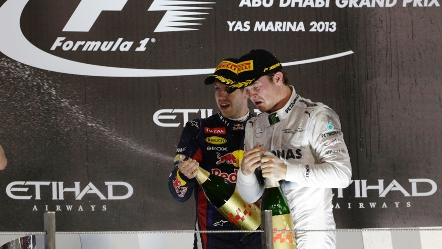 Red Bull driver Sebastian Vettel of Germany, winner, left, and third place Mercedes driver Nico Rosberg of Germany spray rose water as they celebrate on the podium after the Emirates Formula One Grand Prix at the Yas Marina racetrack in Abu Dhabi, United Arab Emirates, Sunday, Nov. 3, 2013. (AP Photo/Hassan Ammar)