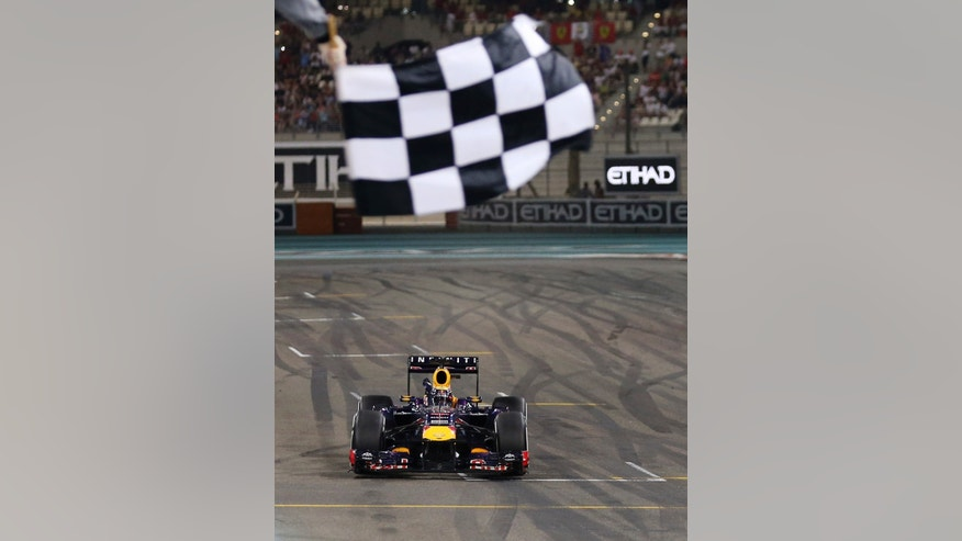 Red Bull driver Sebastian Vettel of Germany crosses the finish line to win the Abu Dhabi Formula One Grand Prix at the Yas Marina racetrack in Abu Dhabi, United Arab Emirates, Sunday, Nov. 3, 2013. (AP Photo/Luca Bruno)