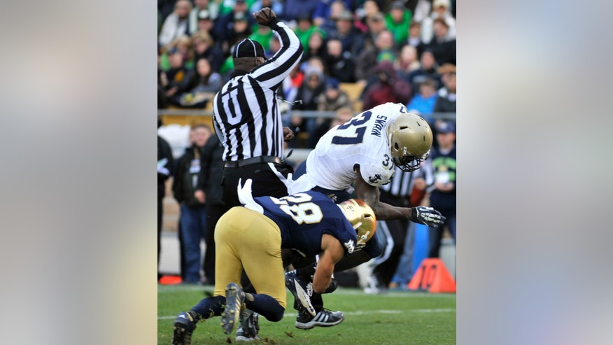 Navy fullback Chris Swain (37) heads towards the end zone for a touchdown as Notre Dame safety Austin Collingsworth (28) tackles him in the first half of an NCAA college football game, Saturday, Nov. 2, 2013, in South Bend, Ind. (AP Photo/Joe Raymond)