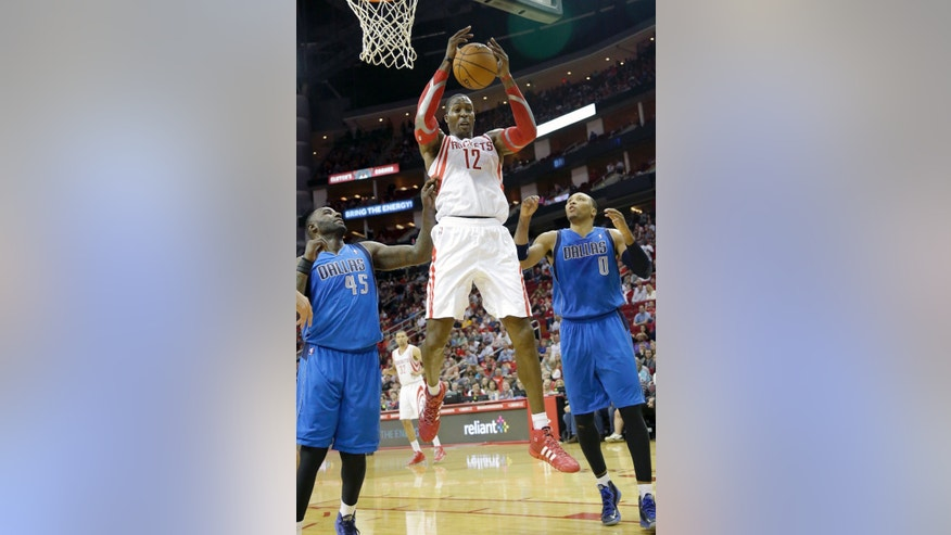 Houston Rockets' Dwight Howard (12) grabs a rebound between Dallas Mavericks Samuel Dalembert (1) and DeJuan Blair (45) in the first half of an NBA basketball game Friday, Nov. 1, 2013, in Houston. (AP Photo/Pat Sullivan)