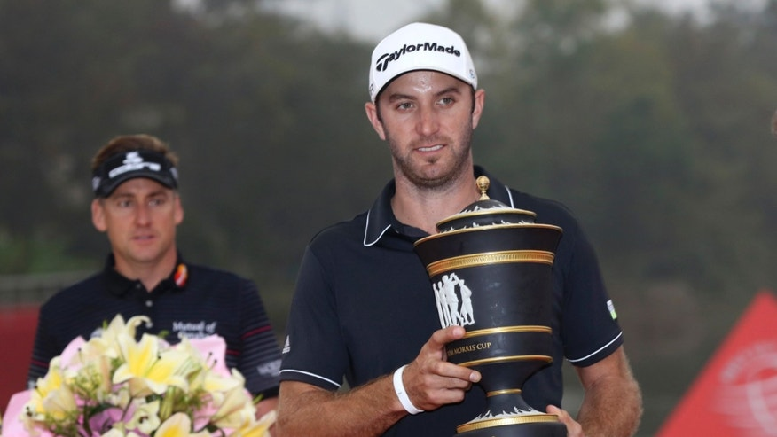 Dustin Johnson of the United States, right, holds his champion trophy as the runner-up Ian Poulter of England, left, holds a bouquet during the award ceremony of the HSBC Champions golf tournament at the Sheshan International Golf Club in Shanghai, China, Sunday, Nov. 3, 2013. (AP Photo/Eugene Hoshiko)