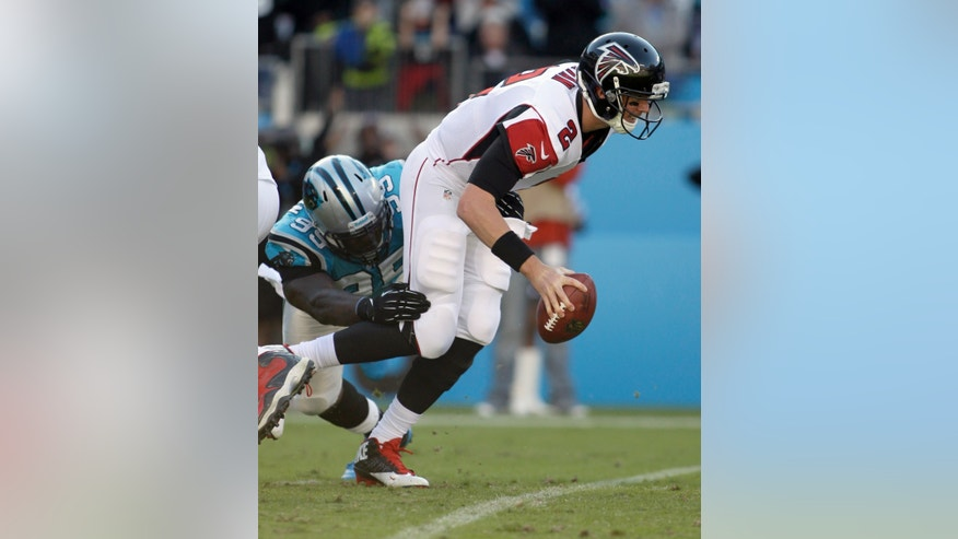 Atlanta Falcons' Matt Ryan (2) tries to get away from Carolina Panthers' Charles Johnson (95) in the second half of an NFL football game in Charlotte, N.C., Sunday, Nov. 3, 2013. (AP Photo/Bob Leverone)