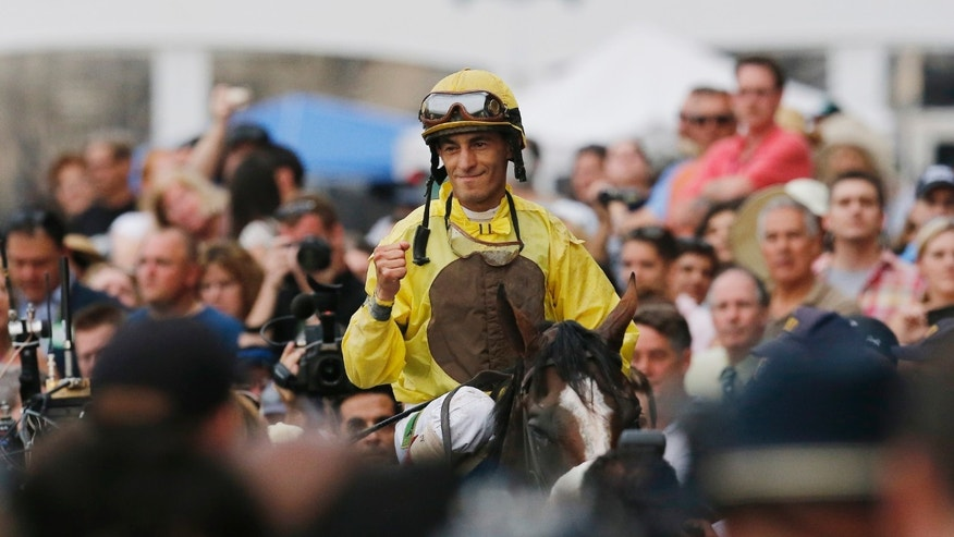 Jockey John Velasquez pumps his fist as he rides Union Rags into the winner's circle after the Belmont Stakes horse race, Saturday, June 9, 2012, at Belmont Park in Elmont, N.Y.  (AP Photo/Mark Lennihan)