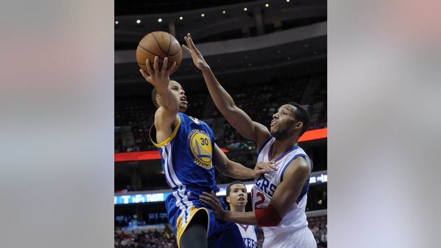 Golden State Warriors' Stephen Curry (30) drives to the basket past Philadelphia 76ers' Evan Turner (12) during the first half of an NBA basketball game on Monday, Nov. 4, 2013, in Philadelphia. (AP Photo/Michael Perez)