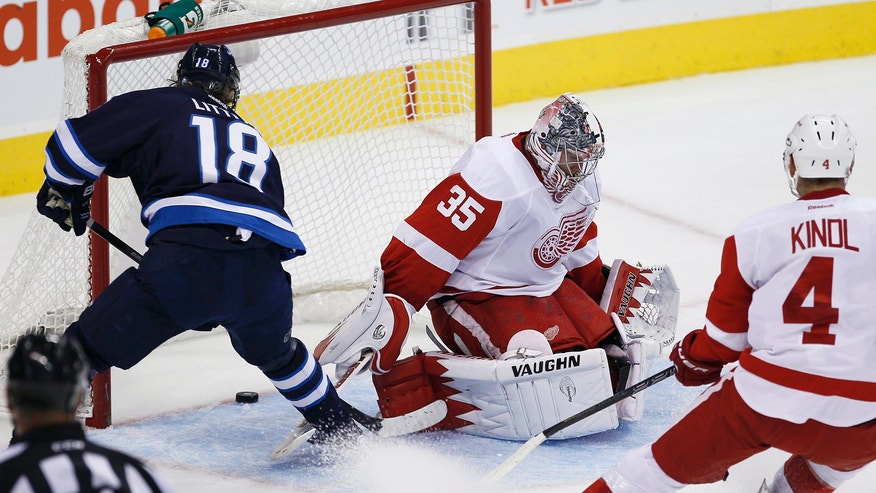 Winnipeg Jets' Bryan Little (18) scores on Detroit Red Wings' goaltender Jimmy Howard (35) and Jakub Kindl (4) during first period NHL action in Winnipeg on Monday, Nov. 4, 2013. (AP Photo/The Canadian Press, John Woods)