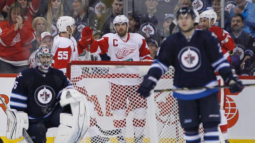 Detroit Red Wings' Niklas Kronwall (55) and Henrik Zetterberg (40) celebrate a goal against the Winnipeg Jets' goaltender Al Montoya (35) during second period NHL action in Winnipeg on Monday, Nov. 4, 2013.  (AP Photo/The Canadian Press, John Woods)