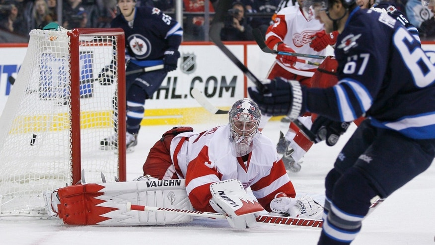 Winnipeg Jets' Michael Frolik (67) scores on Detroit Red Wings' goaltender Jimmy Howard (35) during second period NHL action in Winnipeg on Monday, Nov. 4, 2013.  (AP Photo/The Canadian Press, John Woods)