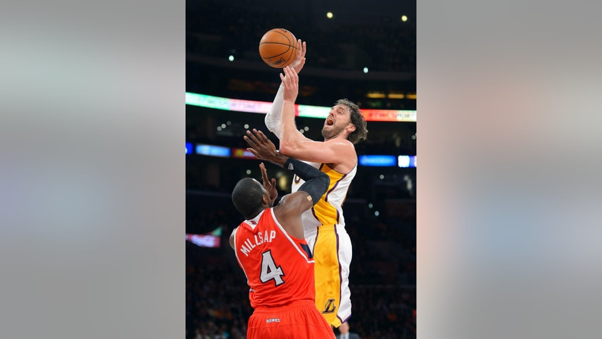 Los Angeles Lakers forward Pau Gasol, top, of Spain, puts up a shot as Atlanta Hawks forward Paul Millsap defends during the first half of their NBA basketball game, Sunday, Nov. 3, 2013, in Los Angeles. (AP Photo/Mark J. Terrill)