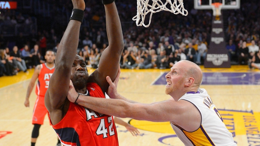 Atlanta Hawks forward Elton Brand, left, is fouled by Los Angeles Lakers center Chris Kaman as he puts up a shot during the first half of their NBA basketball game, Sunday, Nov. 3, 2013, in Los Angeles. (AP Photo/Mark J. Terrill)